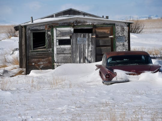 Snow drifts around a car north of Cut Bank, February