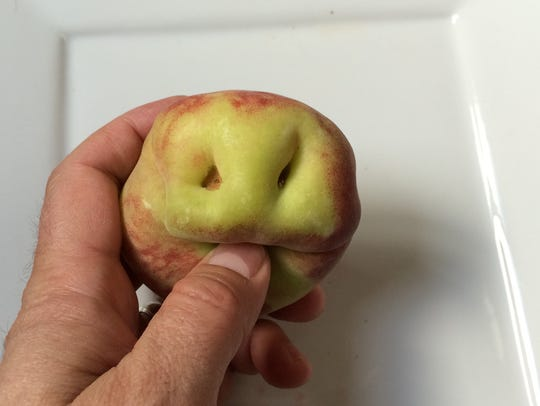 An apple that looks like it has a face is among the