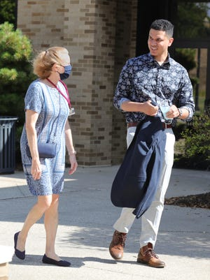 Walsh University graduate Dr. Aaron Palmer arrives with Ann Caplea at the university's Barrette Business and Community Center, where Palmer spoke at a student orientation session on Sunday. Caplea has been a key mentor to Palmer.