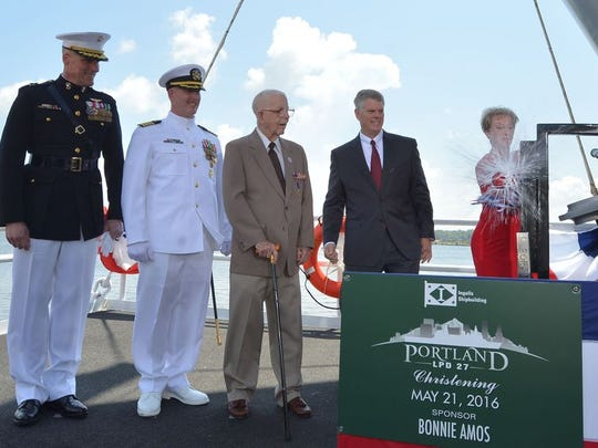 Ship Sponsor Bonnie Amos christens the amphibious transport dock Portland (LPD 27), accompanied by (left to right) U.S. Marine Corps Maj. Gen. Christopher Owens, director of the U.S. Navy's expeditionary warfare division; Capt. Jeremy Hill, prospective commanding officer, Portland; Ted Waller, a World War II veteran who served on the first USS Portland (CA 33); and Brian Cuccias, president of Ingalls Shipbuilding. Portland is the 11th LPD to be built by Ingalls.