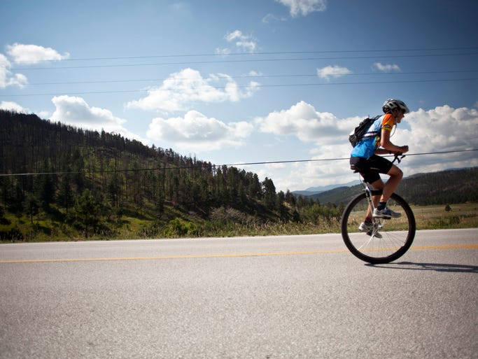 Teagan Brown, 17, rides his unicycle through Rist Canyon during the Pro Challenge Experience Ride Sunday, August 10, 2014.