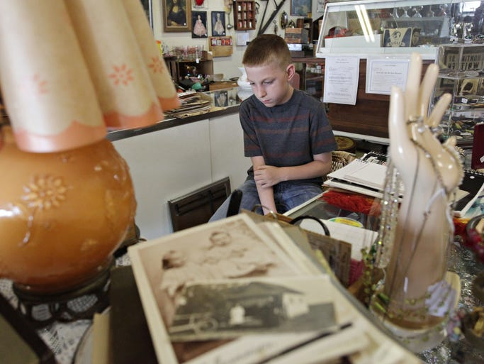 Brock Smith, 10, sits behind the counter at his grandpa's store, Knee Deep Antiques in Sparta on May 27, 2014.