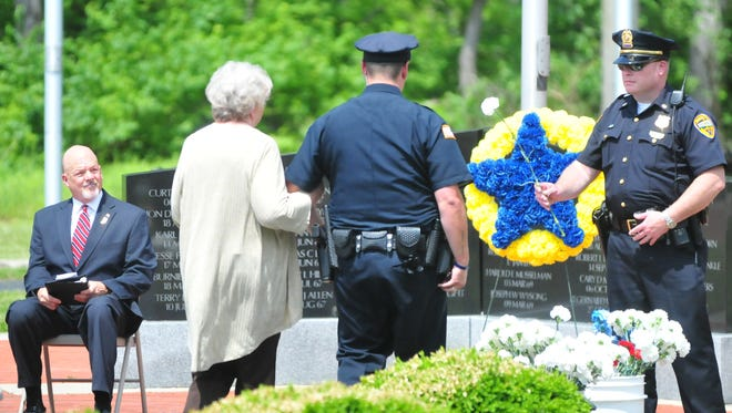 A family member is escorted to place a flower near the memorial wreath in honor of a Wayne County law enforcement officer during the 2017 Peace Officers Memorial Service.