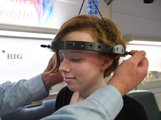 Dr. J. Michael Wattenbarger explains how a halo is attached to Meredith Mozingo's head so she can be placed in traction to help straighten her spine before surgery at the Shriners Hospital for Children in Greenville.