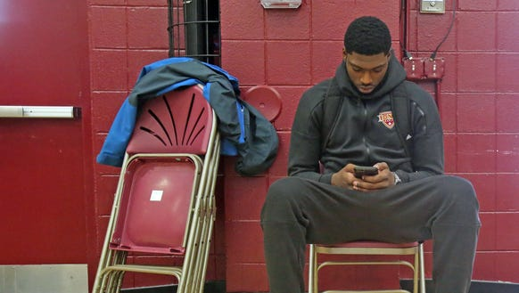 Iona's Roland Griffin is on his phone as he waits for