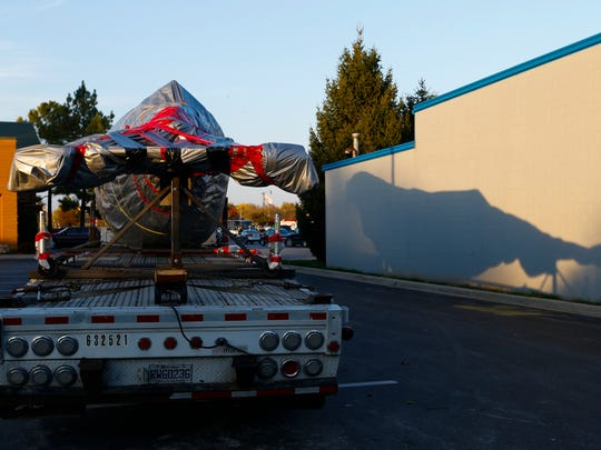 A nearly 40 feet long, and packaged in reams of red and silver, a jumbo-sized mystery object arrived aboard a flatbed trailer.