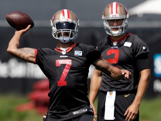FILE - In this Sunday, July 31, 2016 file photo, San Francisco 49ers quarterback Colin Kaepernick (7) throws as quarterback Blaine Gabbert watches during NFL football training camp in Santa Clara, Calif. Colin Kaepernick will get one more chance to impress coach Chip Kelly before the San Francisco 49ers announce their starting quarterback even as the debate surrounding Kaepernick's refusal to stand for the national anthem remains heated. (AP Photo/Marcio Jose Sanchez, File)