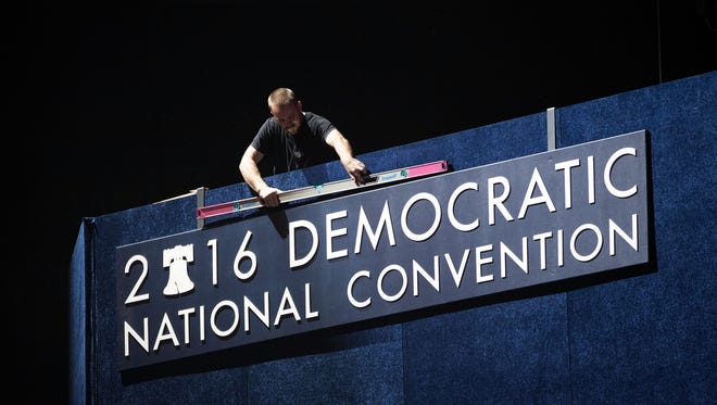 A worker uses a level on signage ahead of the Democratic National Convention at the Wells Fargo Center.