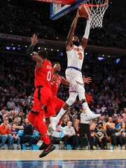 New York Knicks forward Tim Hardaway Jr. (3) goes up to dunk against Toronto Raptors forward CJ Miles (0) and guard Kyle Lowry (7) during the fourth quarter of an NBA basketball game, Wednesday, Nov. 22, 2017, in New York. The Knicks won 108-100.