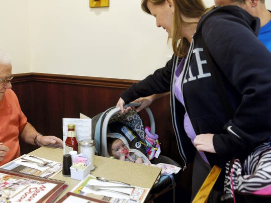 Amy and Nicholas LaPenna of Baltimore, right, get their 2-month-old daughter Ava situated in her car seat on a tray stand for dinner at Mason Dixon Family Restaurant in Shrewsbury. The restaurant is among many family-friendly restaurants in the county.