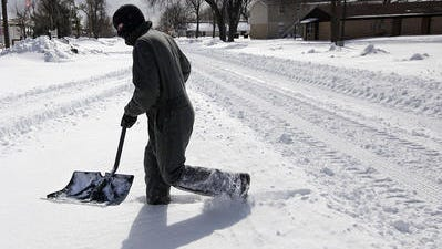 Timothy Carman walks through downtown Oologah, Okla. after shoveling snow.