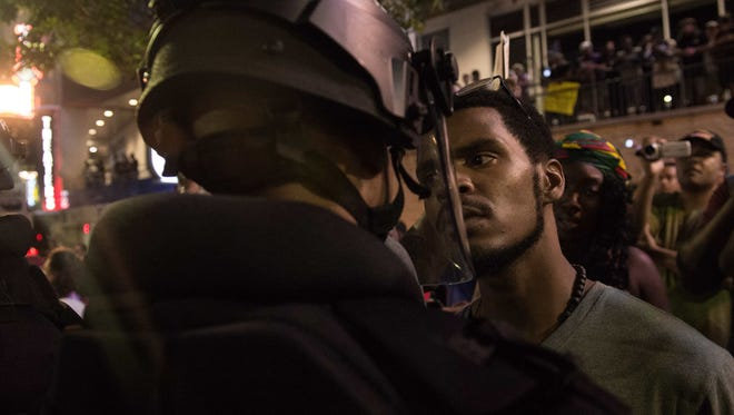A protester stares at riot police during a demonstration against police brutality in Charlotte, N.C., on Sept. 21, 2016.