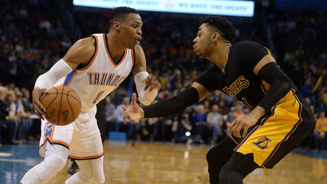 Thunder guard Russell Westbrook (0) drives to the basket in front of Los Angeles Lakers guard D'Angelo Russell (1) during the fourth quarter at Chesapeake Energy Arena. Westbrook's triple-double paced the Thunder to a win on Friday.