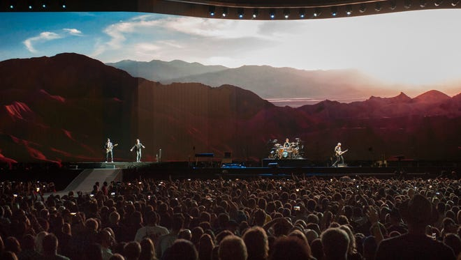 U2 perform in front of a huge panoramic video screen at Ford Field.