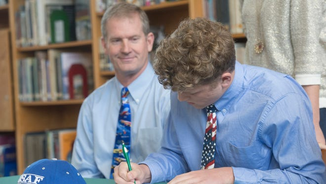 Catholic High School student, Evan, right, signs with United States Air Force Academy during a ceremony at the school Monday morning, while his father, Scott, looks on.