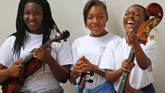 Music students Brian Robb, 12, left, Tiffani Harpp, 10, stand with their instruments during a photo shoot as Nia De Silva, 9, right, breaks into laughter on Oct. 16, 2016 at UM's Frost School of Music's MusicReach program.