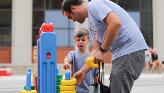 Aaron Hargis and his son Caden Hargis play connect four on their way to Caden's first Colts game during the Bud Light Tailgates on Georgia Street event on Thursday, August 31, 2017.