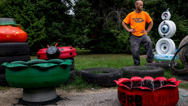 """Joshua Radhs, founder of Michigan Clean Up Our River Banks, stands among some of his """"once junk"""" sculptures made with items retrieved from area rivers Thursday, September 22, 2016 in Port Huron Township. Radhs will be showing his work at A Little Something during the Oct. 14 Art Hop."""