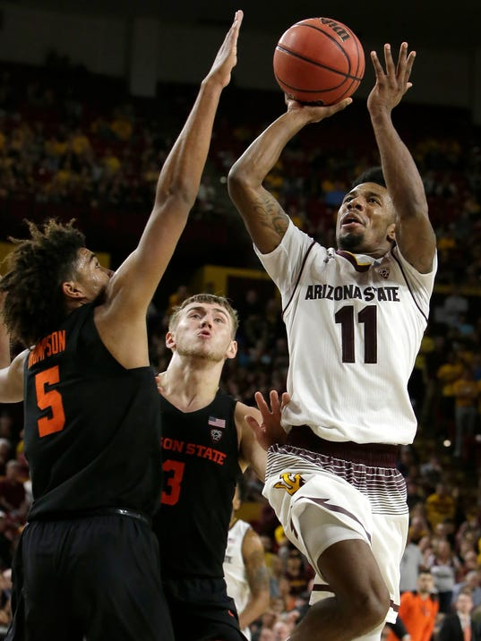 Arizona State guard Shannon Evans II (11) shoots over Oregon State forward Tres Tinkle (3) and Ethan Thompson (5) during the second half of an NCAA college basketball game Saturday, Jan. 13, 2018, in Tempe, Ariz. Arizona State defeated Oregon State 77-75. (AP Photo/Rick Scuteri)