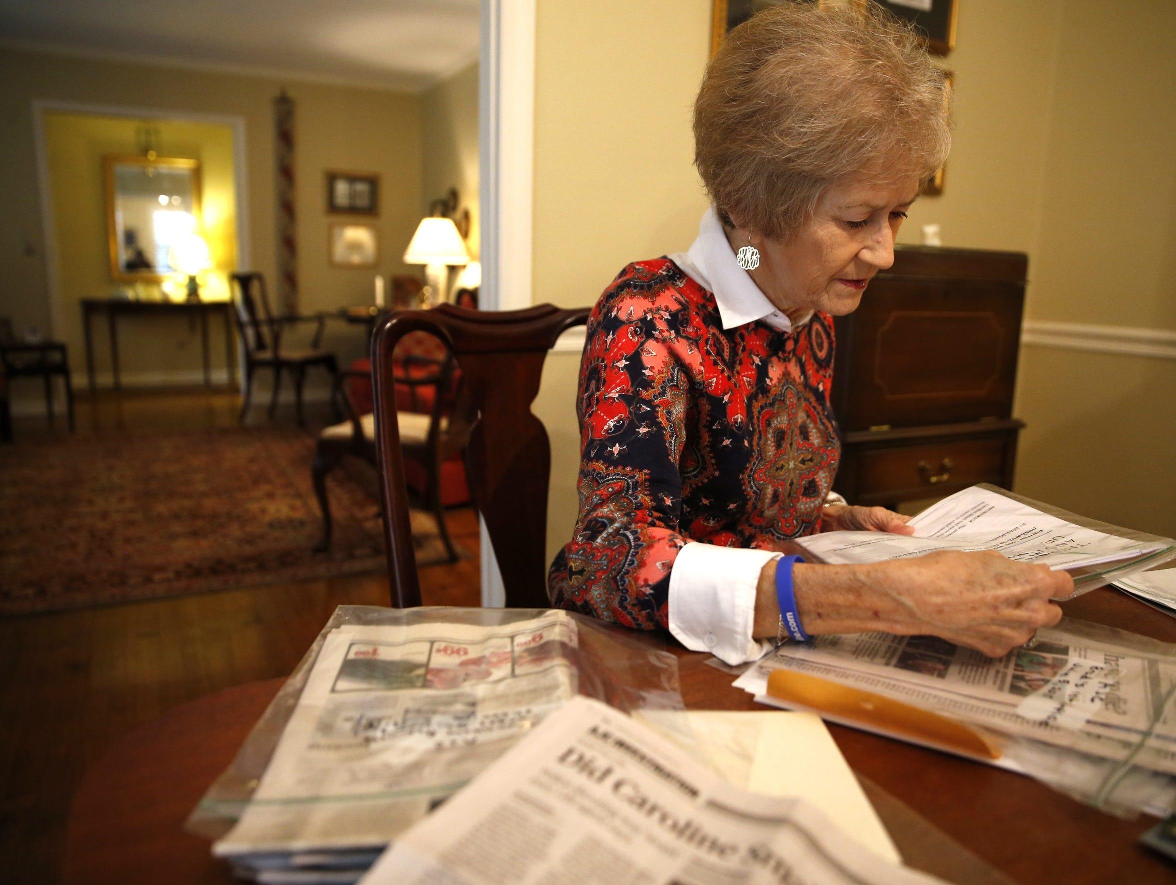 Karen McGehee looks over newspaper clippings, legal