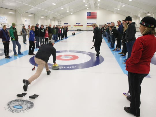 Jay Packard (center), a member of the club, shows how to throw the curling stone to the students gathered around during lessons at Milwaukee Curling Club in Cedarburg.
