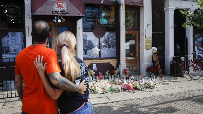 On Aug. 6, 2019, mourners pause at a makeshift memorial for the slain and injured outside Ned Peppers bar in Dayton's Oregon District two days after the mass shooting there.  Facing pressure to take action after the latest mass shooting in the U.S., Ohio's Republican governor urged the Republican-led state legislature to pass laws requiring background checks for nearly all gun sales and allowing courts to restrict firearms access for people perceived as threats.