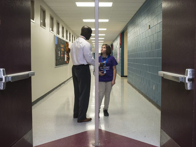 Principal Eric Atuahene (left) talks with Aliyah Rosas