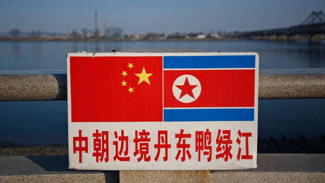 The Chinese and North Korean national flags are seen on a sign along the Yalu River where across is the North Korean town of Sinuiju in Dandong, Liaoning Province, China, 07 April 2013.