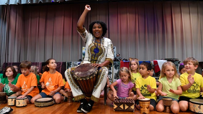 "Elizabeth Kahura cheers as children play drums with her during her presentation Tuesday at the Abilene Public Library. ""Folktales from Africa"" was part of the Young Audiences of Abilene program."