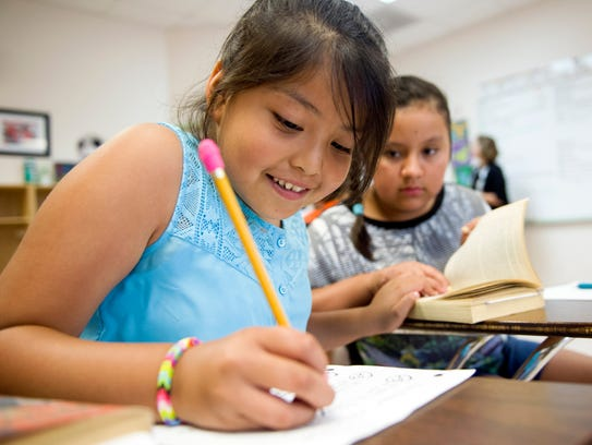 Resurrection Catholic School students Alesson Dayanara, 9, (left) and Ana Enriquez, 10, work on a Harry Potter-themed literary treasure hunt assignment during the school's English summer camp in 2015.