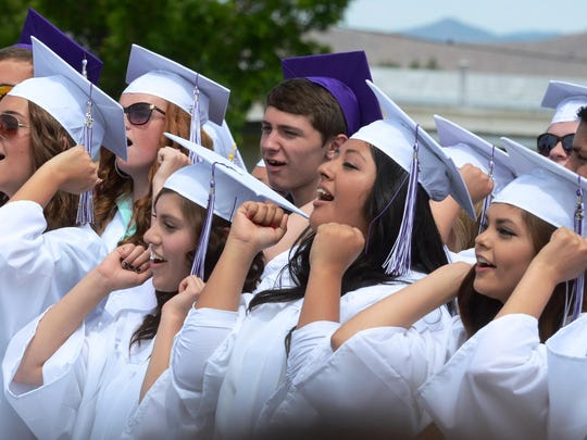 Some Yerington High graduates sing and do the arm motions that go with the YHS school song/alma mater, which they are performing one final time Saturday as a class, a tradition of YHS Commencement exercises, closing the ceremony.