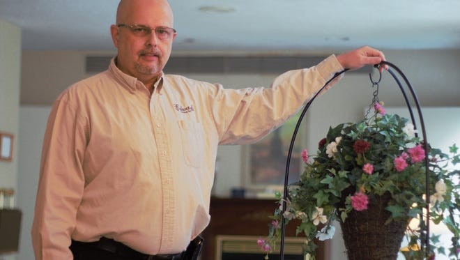 Jeff Edwards stands in the lobby of Hughes-Allen Funeral Home. Edwards recently purchased the business from longtime owner  Kennith Allen and has since taken over operations.