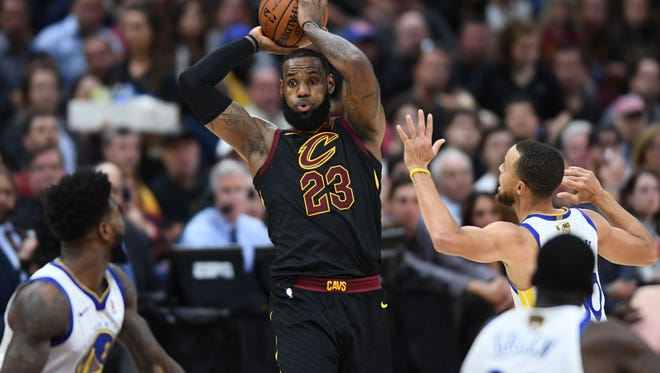 Cleveland Cavaliers forward LeBron James (23) tries to pass the ball against Golden State Warriors guard Stephen Curry (30) during the third quarter in game four of the 2018 NBA Finals at Quicken Loans Arena.