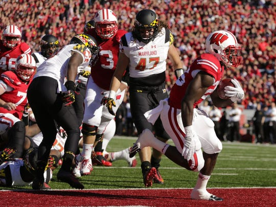 Wisconsin running back Melvin Gordon (25) scores a touchdown against Maryland defensive back Anthony Nixon, left, and Cole Farrand (47) during the first half of an NCAA college football game Saturday, Oct. 25, 2014, in Madison, Wis.