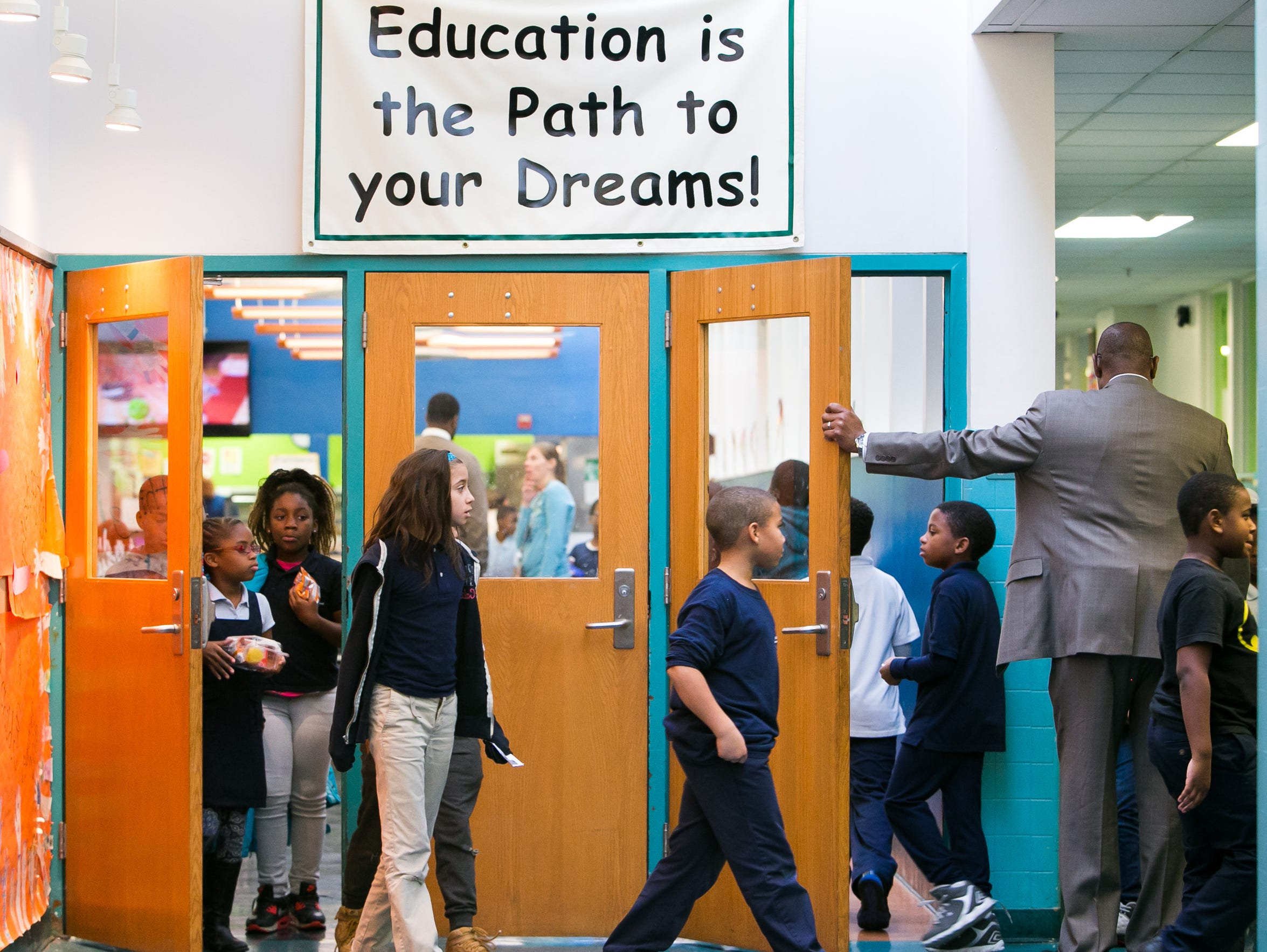 Principal Jeffers Brown holds the door as students arrive for their lunch at Stubbs Elementary School in this file photo. He said the school has held several trauma-informed workshops, which teach staff how to cope with students' emotional and behavioral issues.