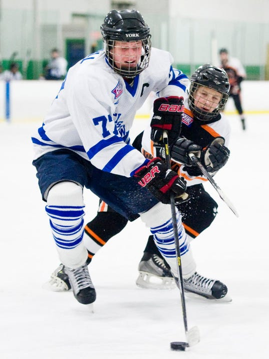 Dallastown's Grant Duvall (77) skates with the puck as Central York's Brandon Linker defends during a recent CPIHL game. (FOR THE DAILY RECORD/SUNDAY NEWS -- JEFF LAUTENBERGER)
