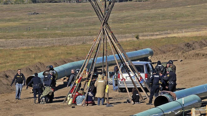 Law enforcement officers, left, drag a person from a protest Monday against the Dakota Access Pipeline, near the town of St. Anthony in rural Morton County, N.D.