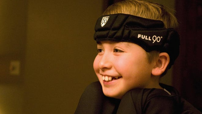 Hayden Shumaker, 10, of Forsyth, Ill., shows the special headgear he wears when he plays sports. He suffered two concussions in 2014.