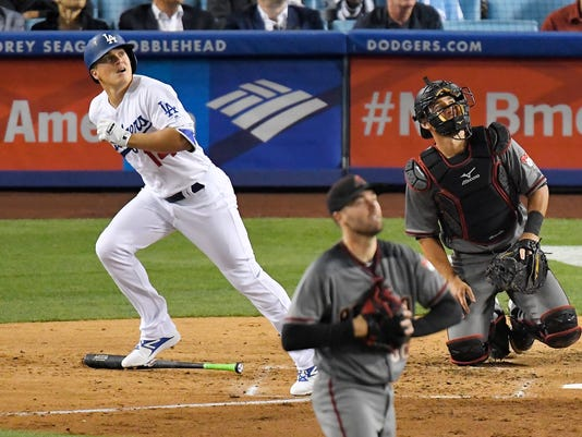 Los Angeles Dodgers' Enrique Hernandez, left, hits a solo home run as Arizona Diamondbacks starting pitcher Robbie Ray, center, and catcher Jeff Mathis watch during the fourth inning of a baseball game, Monday, April 17, 2017, in Los Angeles. (AP Photo/Mark J. Terrill)