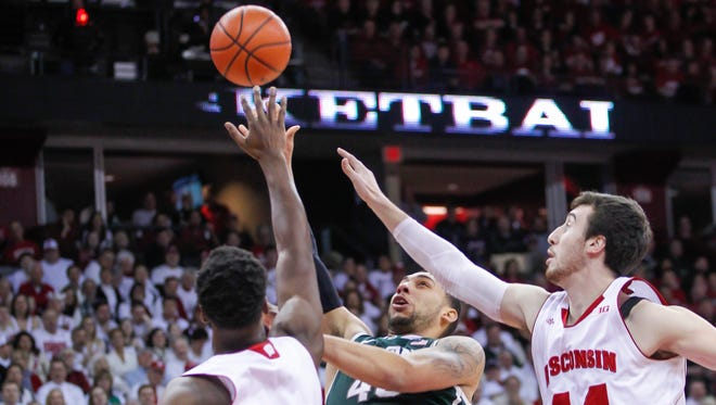 Michigan State's Denzel Valentine, center, shoots between Wisconsin's Nigel Hayes (10) and Frank Kaminsky during the first half of Sunday's Big 10 men's basketball game in Madison.