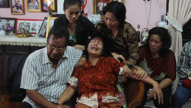 Risman Siregar, left, comforts his wife, Erlina Panjaitan. They are parents of Firman Chandra Siregar, a 24-year-old passenger on missing Malaysia Airlines Flight 370.