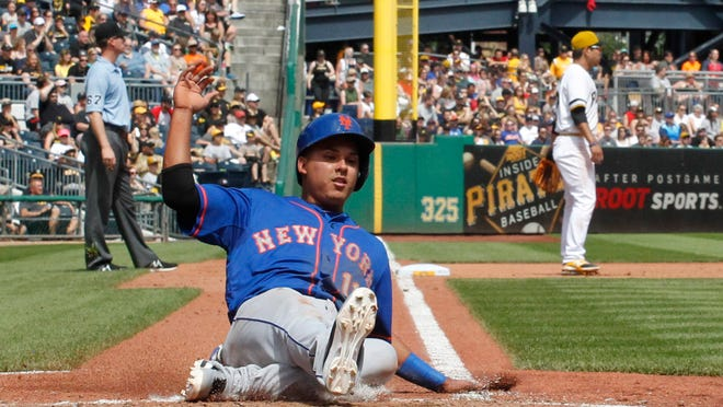 Mets shortstop Ruben Tejada scores against Pittsburgh during the fifth inning at PNC Park. The Pirates won 9-1.