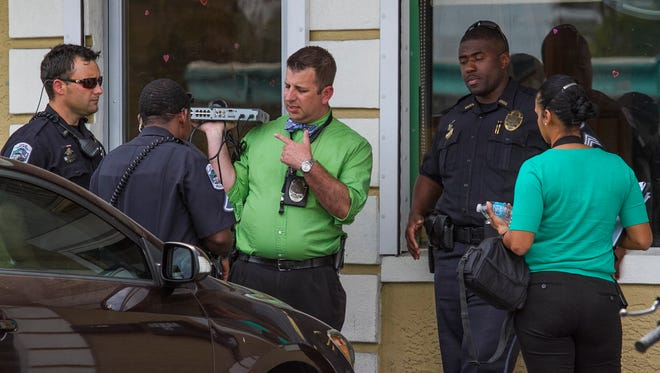 Fort Myers Police Department investigators collect evidence from the scene of a shooting after a fight broke out at Tropical Creole Restaurant about 1:30 p.m.Thursday afternoon.  Three people were shot as a result, none were critically injured.
