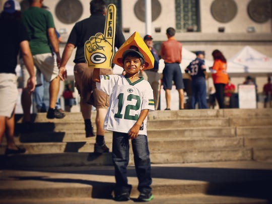 Kaylen Patel, 5, of Bloomingdale, Ill., wears his Green Bay Packers gear as he poses for a family photo Sunday outside Soldier Field in Chicago. Patel lives in a house full of Chicago Bears fans.