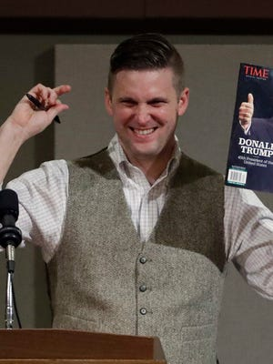 Richard Spencer, who leads a movement that mixes racism, white nationalism and populism, holds up a magazine cover showing President-elect Donald Trump before signing it for a supporter Tuesday, Dec. 6, 2016, in College Station, Texas. Texas A&M officials say they didn't schedule the speech by Spencer, who was invited to speak by a former student who reserved campus space available to the public. (AP Photo/David J. Phillip)