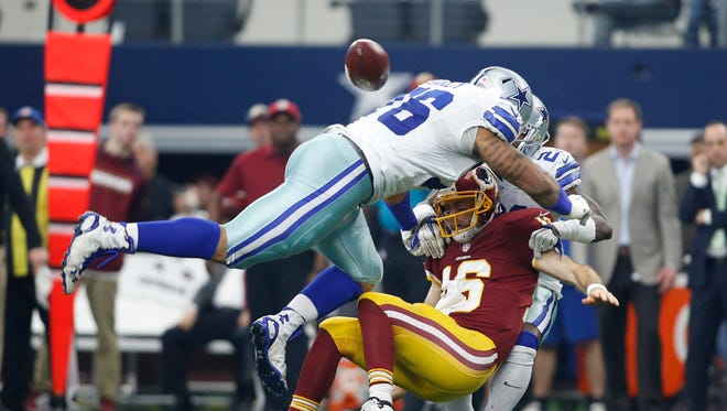 Washington Redskins quarterback Kirk Cousins (8) fumbles the ball after being sacked by Dallas Cowboys defensive end Greg Hardy (76) and cornerback Terrance Mitchell (21) at AT&T Stadium.