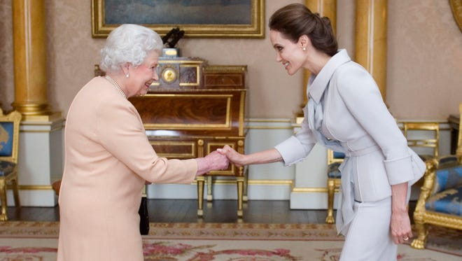 Angelina Jolie, right, is presented with the Insignia of an Honorary Dame Grand Cross of the Most Distinguished Order of St Michael and St George by Britain's Queen Elizabeth II at Buckingham Palace, London, Friday, Oct. 10, 2014.  Jolie received an honorary damehood (DCMG) for services to UK foreign policy and the campaign to end war zone sexual violence.