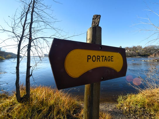 A portage sign is posted on the banks of the Mississippi