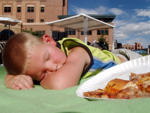 Wyatt Warberg, 4, manages to get some sleep Sunday, June 13, 2004 at the Taste of Fort Collins while band The Smitherines plays. Wyatt had earlier been at Fit For Fun and was all played out.