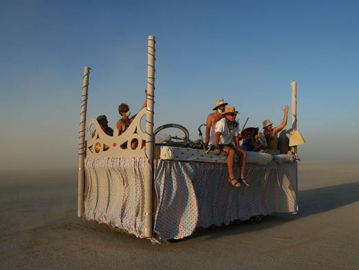 People ride around the Black Rock Desert on an art car at the Burning Man Festival in Black Rock City, Nev., Thursday afternoon, Aug. 28, 2003.
